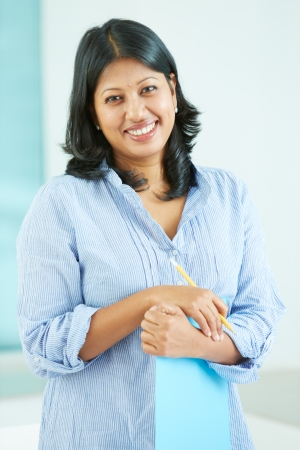 Portrait of happy mature businesswoman with document and pencil looking at camera photo