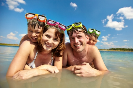family beach: Photo of happy family of divers in water looking at camera Stock Photo