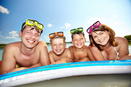 Photo of happy family looking at camera during summer recreation photo