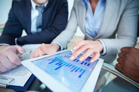 crecimiento personal: Las manos humanas durante la discusión del documento de negocios en la pantalla táctil a satisfacer