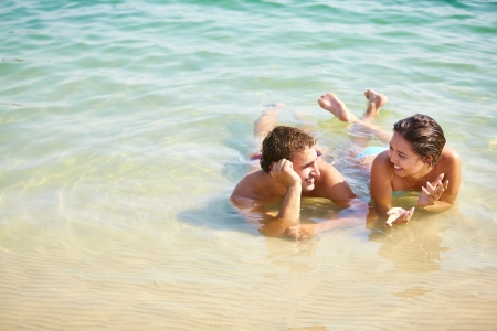 Portrait of a smiling couple lying in warm water and chatting photo