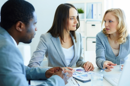 Image of three business partners discussing documents at meeting Stock Photo - 19703430