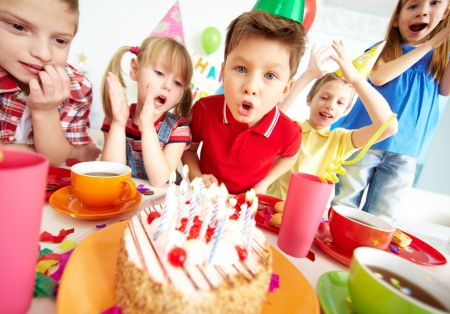 children party: Group of adorable kids having birthday party with festive cake