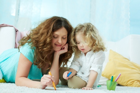 Close-up image of a lovely mom drawing with her little daughter photo
