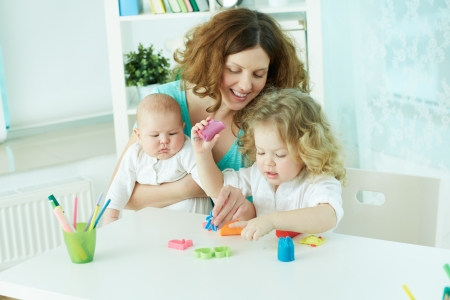 Pretty woman spending time with her children at home photo