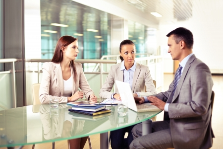 Group of three business partners interacting at meeting in office photo