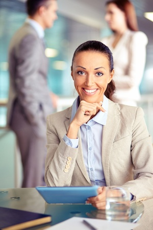 Portrait of confident employee with touchpad looking at camera on background of working colleagues photo