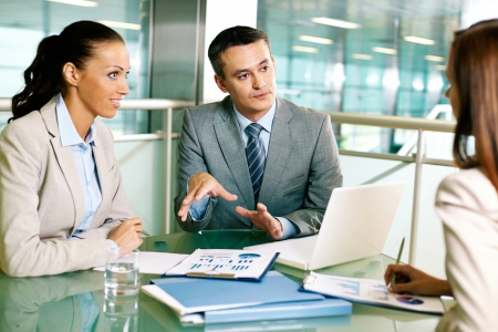 corporate group: Group of business partners interacting at meeting in office