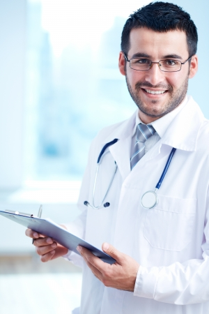 Confident doctor with stethoscope and clipboard looking at camera photo
