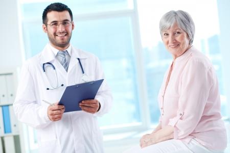 Doctor patient: Seguro m�dico con estetoscopio y el portapapeles y su paciente senior mirando a la c�mara
