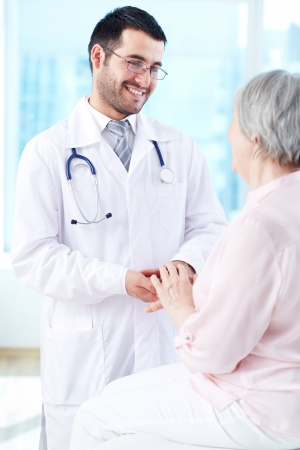 male doctor: Confident doctor looking at his senior patient while speaking to her Stock Photo
