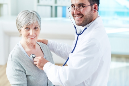 Confident doctor examining his senior patient while both looking at camera photo