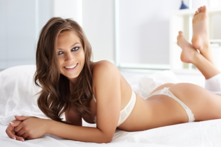 girl bra: Happy young woman in lingerie lying in bed and looking at camera  Stock Photo