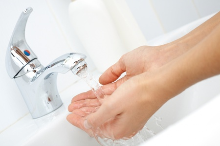 Close-up of human hands being washed under stream of pure water from tap photo