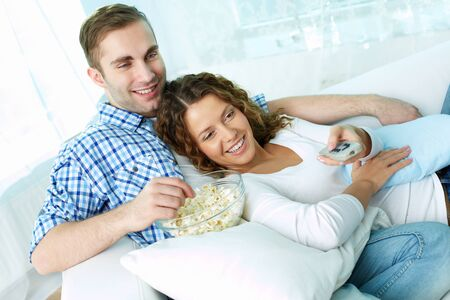 eating popcorn: Young lovers enjoying lazy weekend watching TV and eating pop-corn Stock Photo