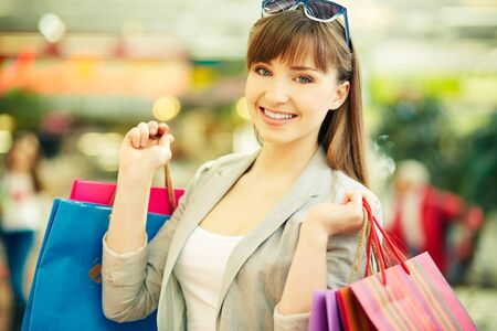 shopaholism: Pretty lady with colorful shopping bags smiling at camera Stock Photo