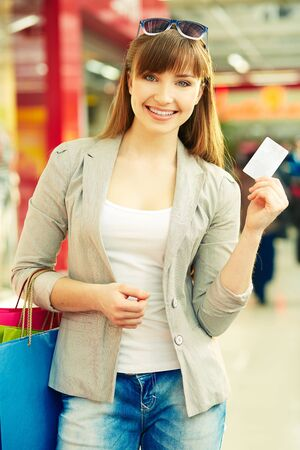 Pretty lady with colorful shopping bags showing credit card photo