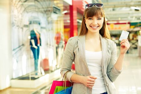 Pretty lady with shopping bags showing credit card photo