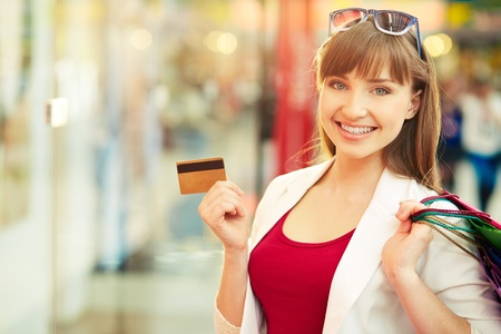 woman holding card: Pretty lady showing credit card in the mall