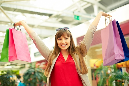 shopaholism: Portrait of smiling girl being satisfied with her lucky shopping