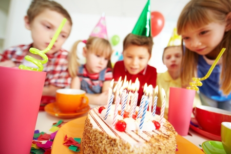 kids birthday party: Group of adorable kids looking at birthday cake with candles