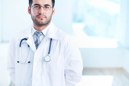 serious doctor: Portrait of serious doctor with stethoscope looking at camera