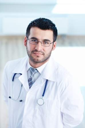 Portrait of serious doctor with stethoscope looking at camera photo