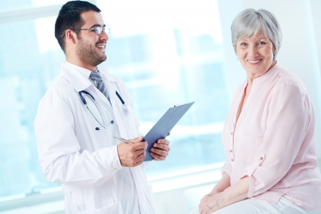 Confident doctor with stethoscope and clipboard speaking to his senior patient while she looking at camera photo