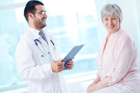 Doctor patient: Seguro m�dico con estetoscopio y el portapapeles de hablar con su �ltimo paciente, mientras que mirando a la c�mara
