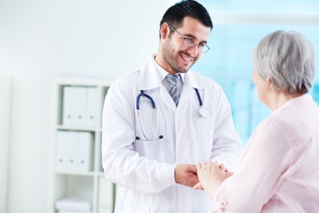 Confident doctor looking at his senior patient while speaking to her photo