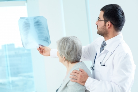 Confident doctor showing x-ray to his senior patient in hospital Stock Photo - 19728935