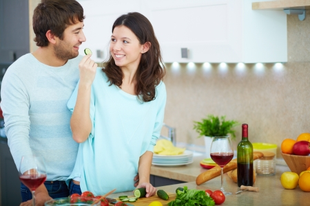 Portrait of young man and his wife cooking vegetable salad in the kitchen  photo