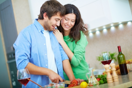 a pair of: Portrait of young man cooking salad and his wife embracing him in the kitchen