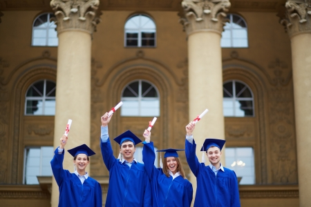 euphoric: Group of smart students in graduation gowns showing their certificates