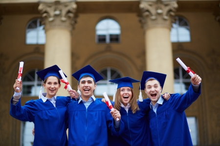 commencement: Group of smart students in graduation gowns holding diplomas Stock Photo