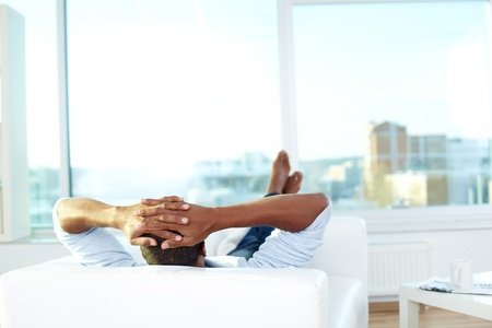 Image of young African man lying on sofa and having rest photo