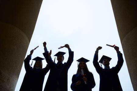 graduacion escolar: Contornos de cuatro graduados con t�tulos fuera Foto de archivo