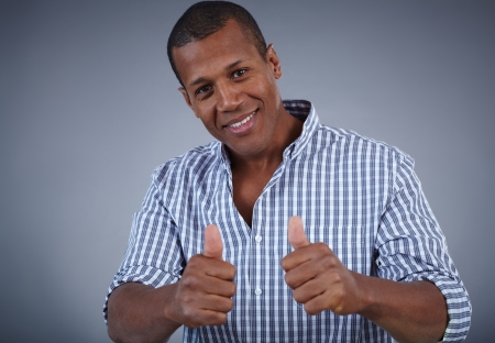 Image of young African man showing thumbs up and looking at camera with smile photo