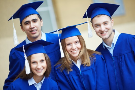 alumnus: Friendly students in graduation gowns looking at camera
