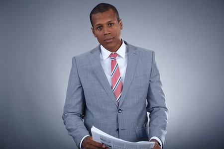 Portrait of successful professional in suit with newspaper looking at camera photo