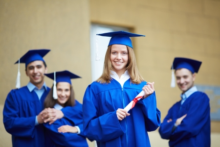 tassel: Friendly students in graduation gowns looking at camera with happy girl in front