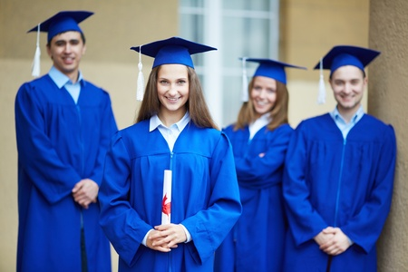 alumnus: Friendly students in graduation gowns looking at camera with happy girl in front
