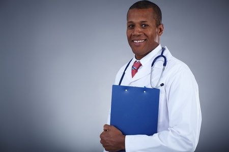 Portrait of confident doctor with clipboard looking at camera photo