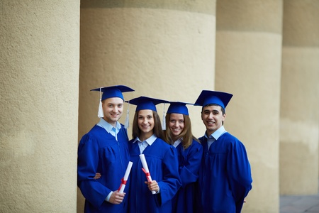 alumna: Group of smart students in graduation gowns holding diplomas and looking at camera