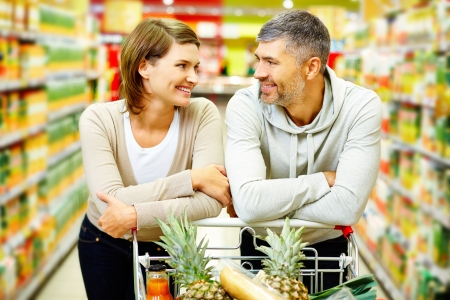 Image of happy couple with cart looking at one another in supermarket photo