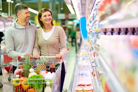 woman shopping cart: Image of happy couple with cart choosing products in supermarket Stock Photo