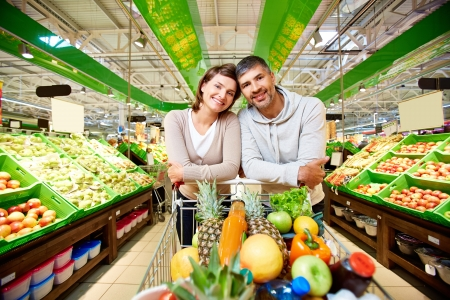 health food store: Image of happy couple with cart full of products looking at camera in supermarket Stock Photo