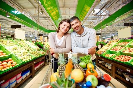 personas saludables: Imagen de la feliz pareja con el carro lleno de productos que mira la c�mara en el supermercado Foto de archivo