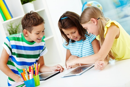 niños estudiando: Retrato de compañeros felices en el lugar de trabajo utilizando tabletas digitales
