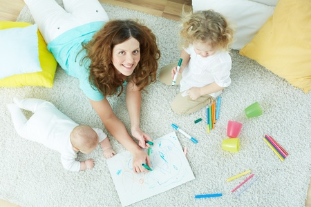 looking after: The above-view portrait of a beautiful babysitter looking after cute kids